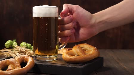 pretzel : Man hand takes a glass of light beer from a dark wooden table. Stock Footage