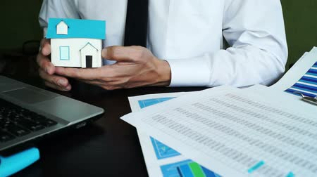 financiamento : Real estate agent holding model of home in an office. Buying or selling house. Vídeos