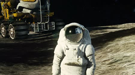 roket : An astronaut on the moon next to his moon vehicle watching the Earth. Stok Video