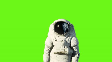 lunar surface : An astronaut on the moon next to his moon rover watching the Earth. Green screen.