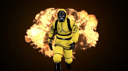 fire suit : A man in a protective suit walks against the background of smoke and explosions. Loopable Background. Stock Footage