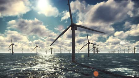 clean electricity production : Offshore windmill farm in the ocean, windmills isolated in the ocean on a beautiful Sunny bright day against the blue sky Stock Footage