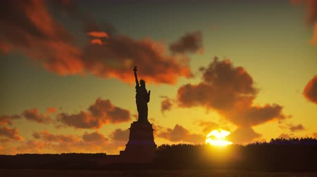 heykel : Statue of Liberty at sunrise, with the new York skyline and sunrise, sky with clouds in the background.