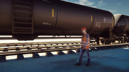 mozdony : Oil worker walks past the railway with Rail tank cars driving on it.