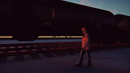 mozdony : Oil worker walks past the railway with Rail tank cars driving on it at sunset