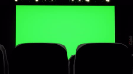 初演 : Cinema interior of movie theatre with blank movie theater screen with green screen and empty seats. Movie entertainment concept. 動画素材