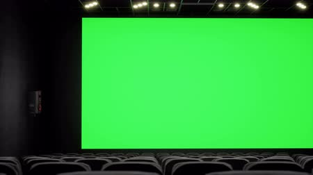 premiere : Cinema interior of movie theatre with blank movie theater screen with green screen and empty seats. Movie entertainment concept. Stock Footage