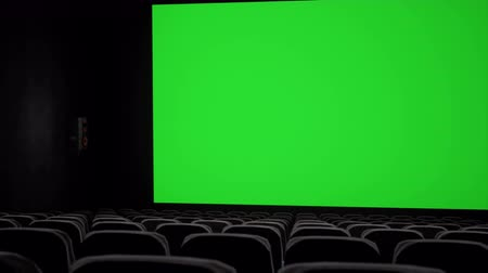 lugares sentados : Cinema interior of movie theatre with blank movie theater screen with green screen and empty seats. Movie entertainment concept. Stock Footage