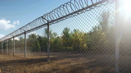 запрещенный : The suns rays and autumn trees are visible through the metal prison fence with barbed wire.