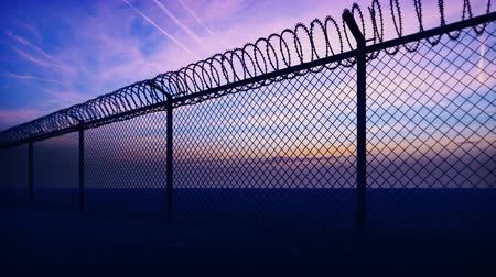 gaiola : Clouds and a sunset can be seen through the metal prison fence with barbed wire. Loop realistic 3D animation. Vídeos