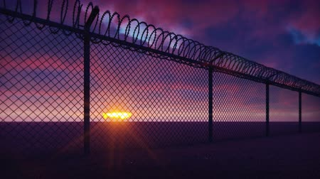 restraint : Through a metal prison fence with barbed wire visible clouds and a disturbing sunset. Loops realistic 3D animation.