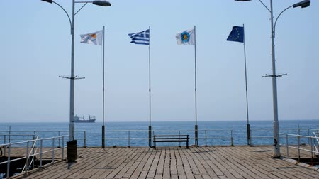 Various flags fluttering in the wind in the morning on the pier in the ancient Greek city of Limassol