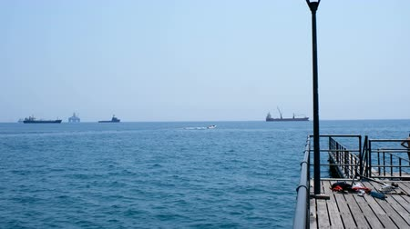 Shot of the open sea on a clear day. Blue sky, pier, ships in the distance and boundless horizon.
