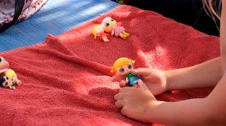 poppetjes : Cute girl playing with her dolls on a sunbed on a sandy beach on a sunny day.