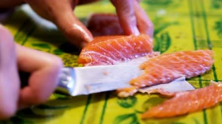 Woman cuts fish fillet, cook prepares fish for cooking, fish dishes, healthy and diet food