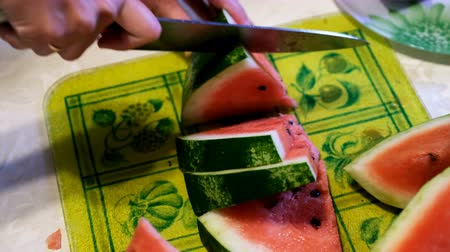 A womans hand cuts watermelon fruit with a knife on a cutting Board in the kitchen. 影像素材