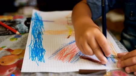 pré escolar : Happy child draws fairy-tale character with felt-tip pens on paper Stock Footage