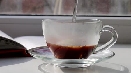 Pour boiling water in a cup of coffee on a sunny window Stok Video
