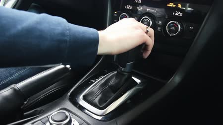 Female hand shifts gears. Automatic transmission, automatic gear shift, is moved from P to D. Park to Drive Wideo