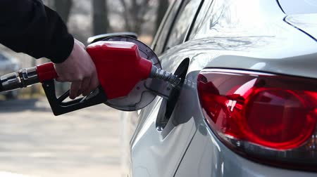 Closeup of man filling benzine gasoline fuel in car at gas station