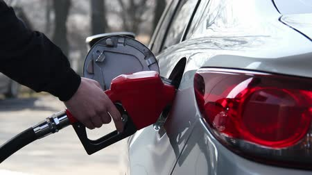petróleo : Closeup of man filling benzine gasoline fuel in car at gas station