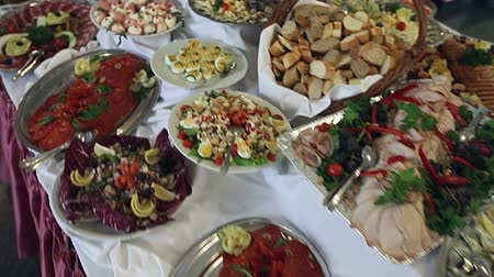 ebéd : Food served on the table - a.k.a. swedish table: meat, rice, pasta, salads and various cakes and pastries - cheese cake and similar and fruits (apples, bananas, oranges), moving steadicam shot