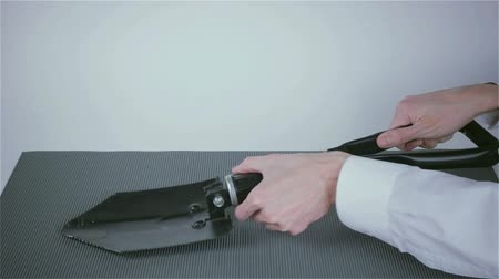 unearth : Black folding shovel in the hands of a businessman Stock Footage