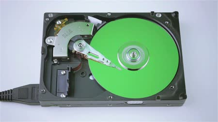 inside bus : Isolated hard drive from the computer with a green disc, green chroma key. Principle of operation. Removing the outer cover, the work head in HDD.