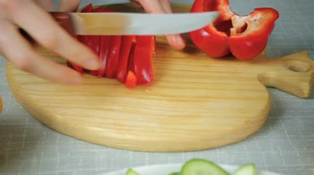 peper : The girl with a knife on the board cuts ripe red bell pepper Stock Footage