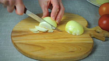 soğancık : Girl chef cuts a piece of yellow onion on a wooden board.