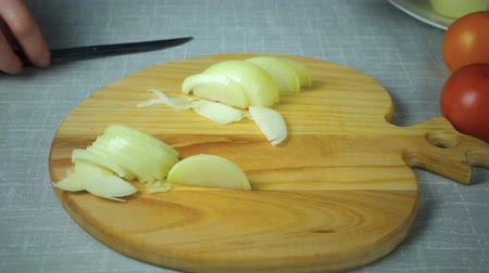 ve slupce : Girl chef cuts a piece of yellow onion on a wooden board.