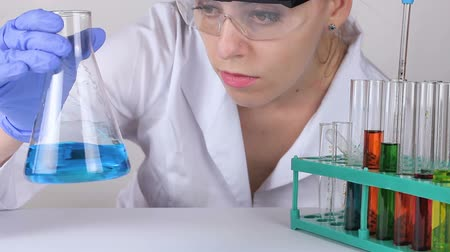 examinando : A young woman doctor stirs the liquid in a flask in laboratory