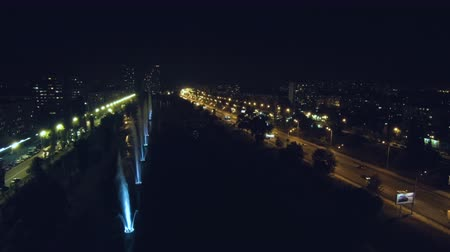 artificial color : Night flight with a quadrupter over singing, musical fountains. Splashes of fountains with color accompaniment. The river next to the road. Stock Footage