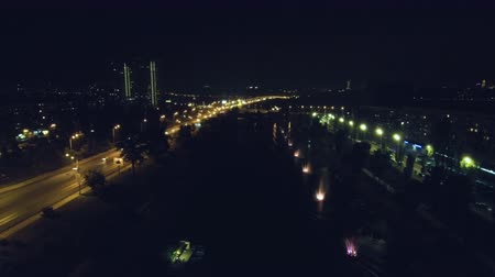 akşam : Aerial Drone Flight Footage: Night flight with a quadrupter over singing, musical fountains. Splashes of fountains with color accompaniment. The river next to the road. Stok Video