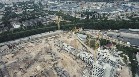 dach : Aerial Drone Flight 4k Footage: The construction crane and the building against the blue sky. Flying over construction of several houses with building cranes. Wideo