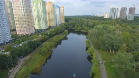 Aerial Drone Flight Footage: View of the beautiful park in the city center. Beautiful colorful houses near the lake and the park.