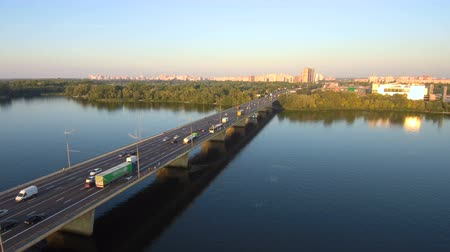 preso : Aerial Drone Flight Footage: View of the bridge over the river with cars. Stream of cars on the bridge, sunset