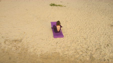 hatha : Aerial view from Drone: A young girl practices yoga by the river. Exercises against the background of the river, the shore and the bridge.