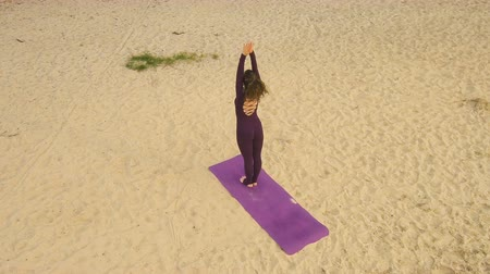 Aerial view from Drone: A young girl practices yoga by the river. Exercises against the background of the river, the shore and the bridge.