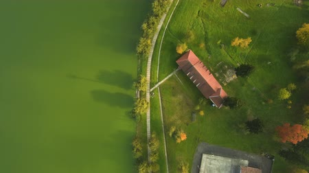 Aerial view from Drone: Embankment of a green lake in a populated city.