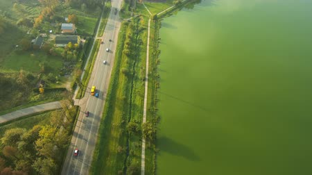 Aerial view from Drone: Road with a car along the autumn trees and green lake.