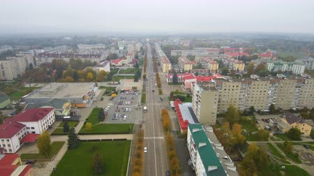 Aerial view from Drone: Small town with a road and cars, houses and parking lots. Wideo