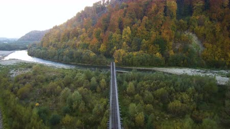 Aerial, top view from Drone: Railway through the river into the forest. Autumn time.