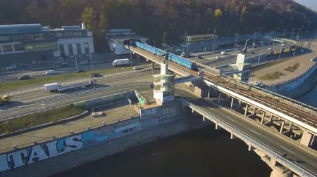 Aerial, top view from Drone: An underground train travels over a bridge with cars and trucks. Wideo