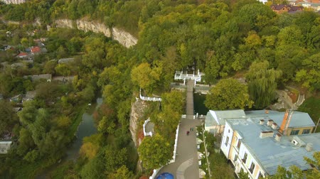 Aerial, top view from Drone. Park with a waterfall in Kamenetz Podolsky. Mountain with waterfall, park and swans. Autumn time.