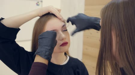 plucks : Master corrects eyebrows, gives shape and thread plucks eyebrows in beauty salon. Professional face care
