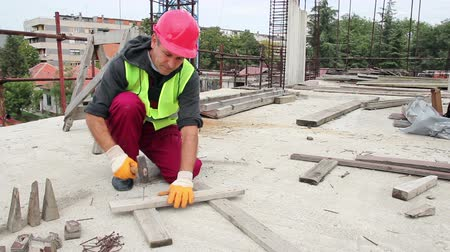 unha : Manual worker with red helmet crouching and hammering nails to wooden plank on construction site. HD1080p. Stock Footage