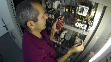 energetyka : Plant electrician testing voltage in the control cabinet.HD1080p.