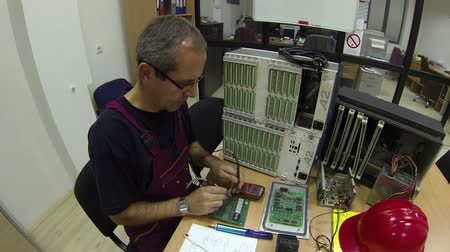 forma : Engineer sitting, examining circuit board with digital multimeter and writing.HD1080p.GoPro HERO3.