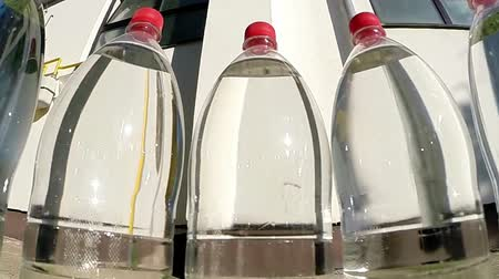 woda mineralna : Spring water bottles arranged in a circle against the sun slow motion.HD1080p. GoPro HERO3.